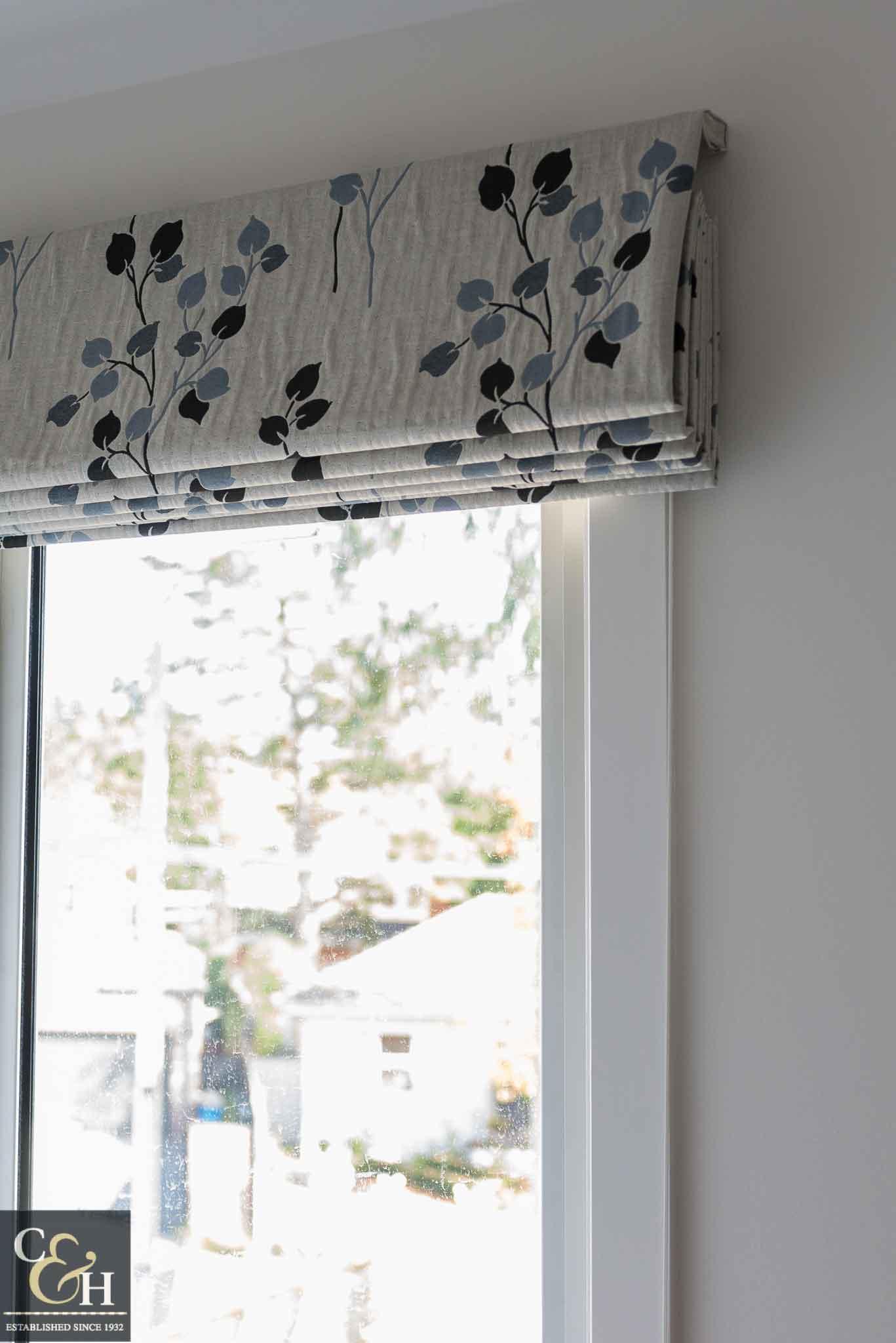 Designer fabric roman blinds 46 on a window.