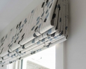 Designer fabric roman blinds 47 on a window.