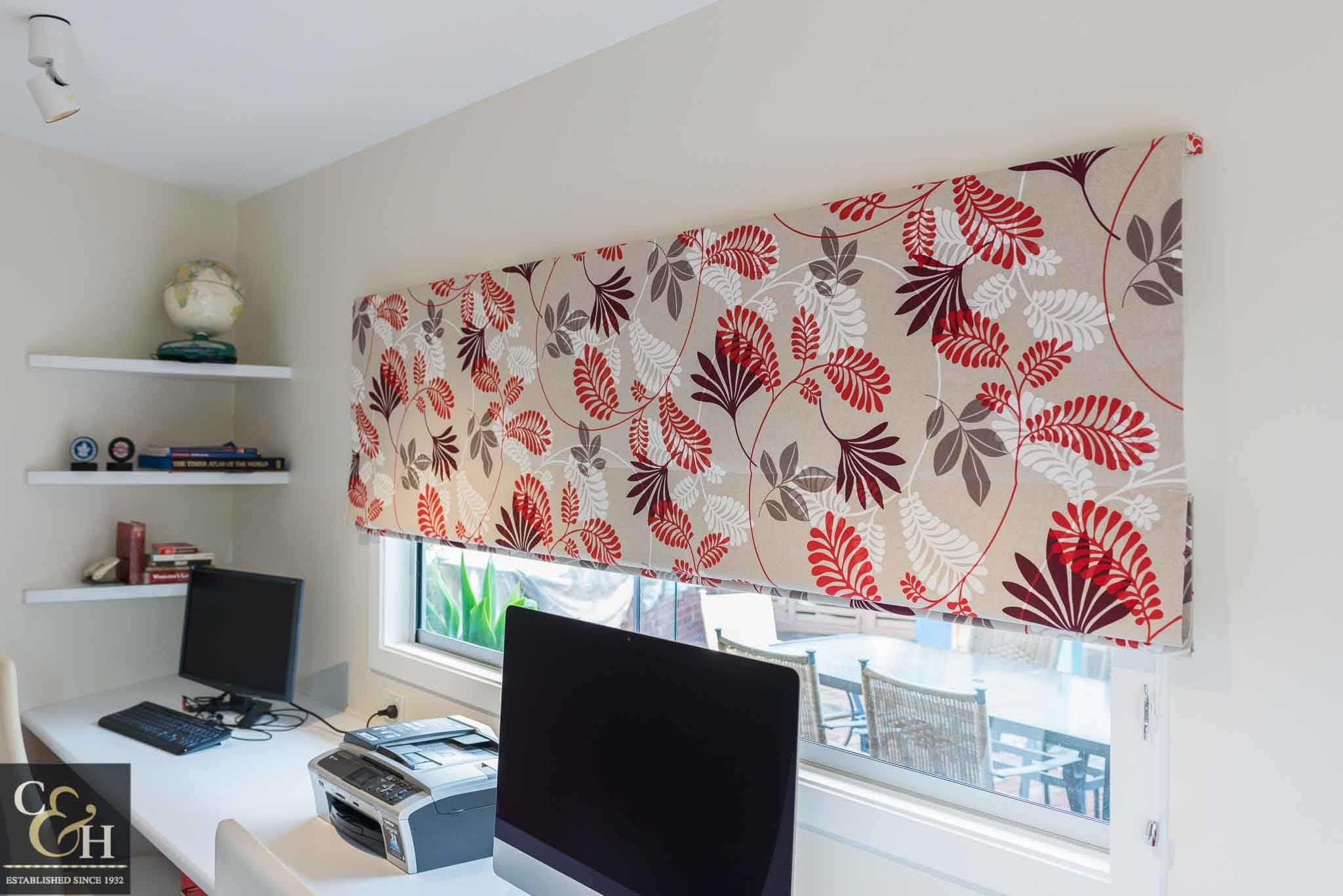 Designer fabric roman blinds 51 on a window.